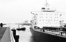 Zeeschip met sleepboten op het kanaal bij brug Sluiskil.