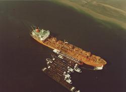 Zeeschip en binnenvaartschepen op de boeien in de Sloehaven.