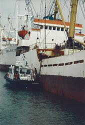 Vaartuig van de Koninklijke Marechaussee langszij een zeeschip in de...