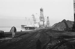 Het lossen van schepen met drijvende kranen aan de kade bij Ovet in de...