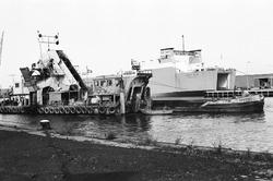 Baggerwerkzaamheden in de Zevenaarhaven. Op de achtergrond een schip...