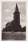 Ringbaan-Oost, R.K. H. Sacramentskerk gezien vanaf de Nieuwe Bosscheweg. Links naast de kerk de Pelgrimsweg. De kerk werd op 21 april 1933 in gebruik genomen onder pastoor J.W.A.       van Oorschot. Kerk en pastorie werden gebouwd onder architectuur van M. van Beek uit Eindhoven. De plechtige consecratie door mgr. Diepen vond plaats op Sacramentsdag 15 juni       1933.