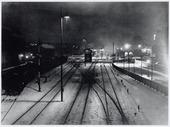 Spoorwegen, Goederenemplacement, N.S.: Spoorwegemplacement in wintertooi vanaf voetgangersbrug aan de Gasthuisstraat bij avond.