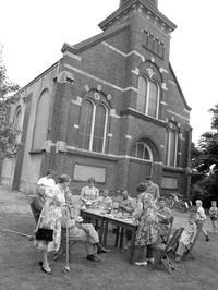 gemeenteleden drinken gezamelijk koffie tijdens het opknappen van hun kerk