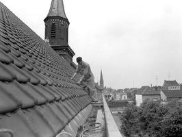 gemeenteleden repareren het dak van hun kerk
