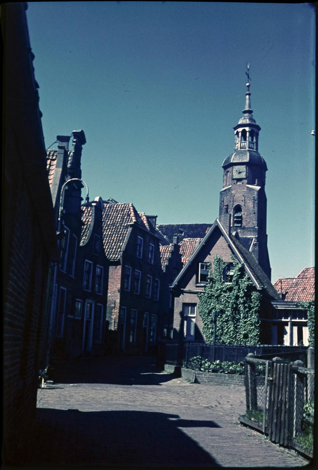 Huizen aan pleintje met daarachter de Ned. Herv. kerktoren