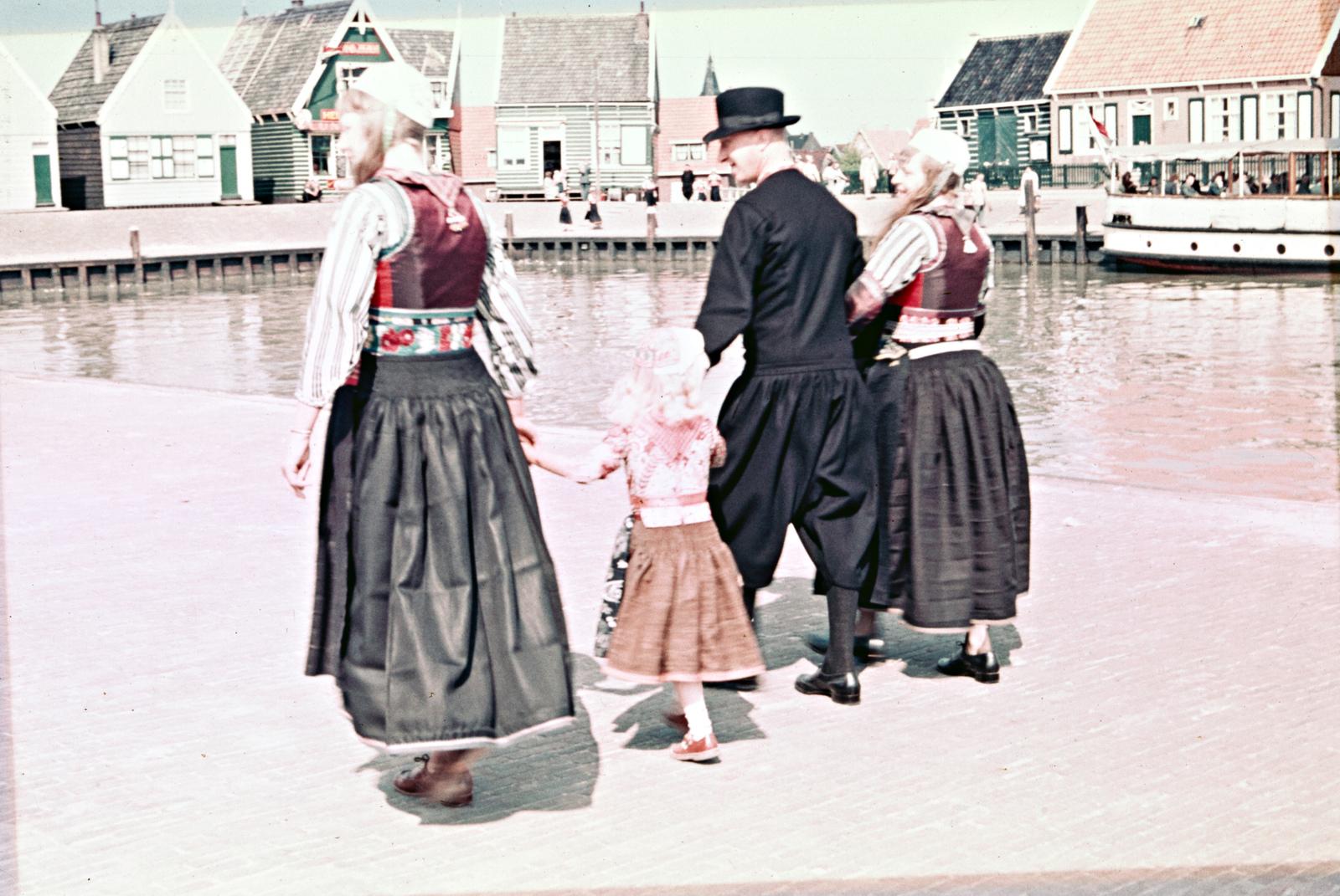 Drie volwassen en een kind in dracht bij de haven