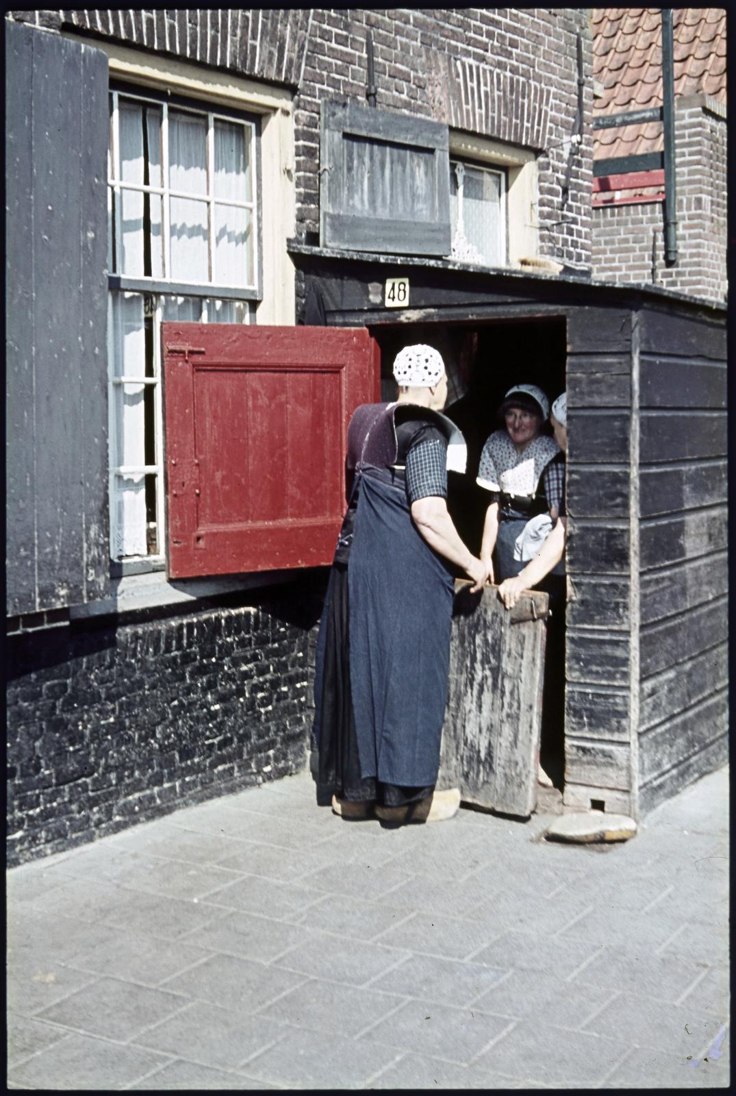 Vrouwen in klederdracht bij schuurtje met geopende halve deur.