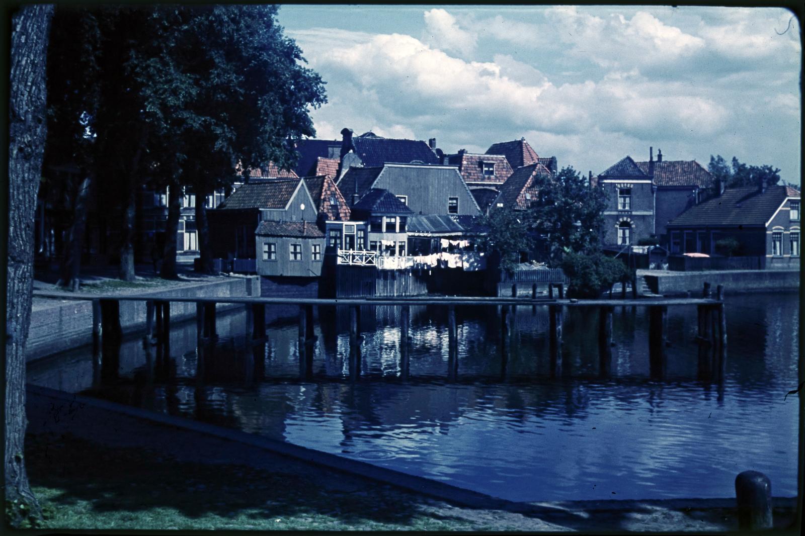 Loopsteiger in haven met huizen in de verte