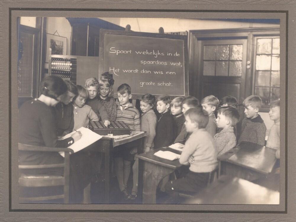 Schoolsparen. Op het bord staat: Spaart wekelijks in de spaardoos wat, Het wordt dan wis een groote schat. Foto met spaarkist, tevens geplaatst in de Heldersche Courant