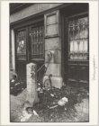 Gevel met stoephek aan de Bloemgracht 77. De stoep ligt vol afval. Op de muur st…