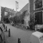 Amstelveld 10 (ged.), Amstelkerk met klokketoren, links de zijgevel van Regulier…