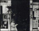 Prinsengracht 228, meisje in deuropening van winkel