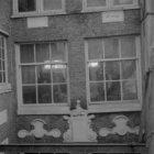 Gevelsteen in de achtergevel van Keizersgracht 704 aan een binnenplaats met een …