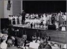 Linnaeusstraat 2-2A-2C. Honderdvijftig kinderen zingen in de aula van het Tropen…