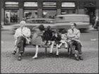 Mensen op een bankje voor Dam 20, kledingzaak Peek & Cloppenburg