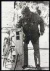 Een man doorzoekt een prullenbak op het Damrak op zoek naar iets eetbaars