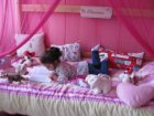 Lezend kind op een roze bed met knuffels in een woning aan de Prof. J.H. Gunning…