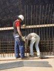 Betonvlechters aan het werk op de bouwplaats van de busterminal De Ruijterkade