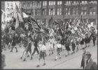 Jongeren marcheren tijdens Bevrijdingsdag 1946 met vlaggen op de Dam. Op de acht…