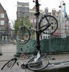 Fiets in lantaarnpaal op de Nieuwmarkt. Op de achtergrond Nieuwmarkt 30-40 (v.r.…