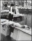 Een kleine woonboot ligt half gezonken in de Prinsengracht