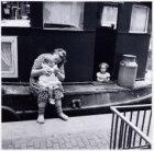 Een moeder met haar kinderen op een vrachtschip aan de Geldersekade