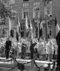 Kinderen met vlaggen bij de feestelijke onthulling van een monument voor Koningi…