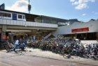 Op straat gestalde fietsen voor de fietsenstalling bij de hoofdingang van Statio…