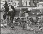 Twee mensen op een bankje voeren de duiven op de Dam