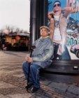 Man zittend op bankje op het Buikslotermeerplein in Amsterdam-Noord
