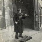 Melle Jacob Scheepstra (1903-1989), viool spelend bij de ingang van de Nieuwe Ke…