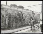 Schoolkinderen en buurtgenoten maken een muurschildering op het spoorwegviaduct …