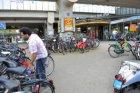 Buiten de fietsenrekken gestalde fietsen bij de hoofdingang van Station Amsterda…