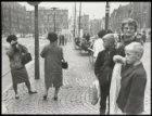 Dam, toeristen en vrouw in klederdracht met kinderen