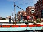 Vrouw hangt de was op aan een waslijn van een woonschip in het Westerdok gezien …