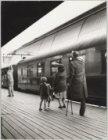 Mensen zwaaien een vertrekkende trein uit op het perron van het Centraal Station