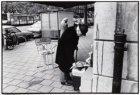 Een man bekijkt een krant bij de AKO boekwinkel in de Beethovenstraat