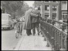 Een laveloze man wordt door een andere man ondersteund op Brug 88 in de Lijnbaan…