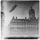 Zeppelin boven het Koninklijk Paleis op de Dam. Links de ingang van de Paleisstr…
