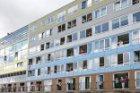 Bewoners van woongebouw Silodam hangen uit de ramen tijdens Sail Amsterdam