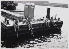 Bouwvak: Bouwvakkers tijdens schafttijd op de Javakade vissend in de IJ-Haven