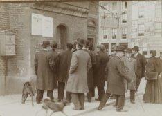 Groep mensen leest mededelingen, aangebracht op de Munttoren, Muntplein