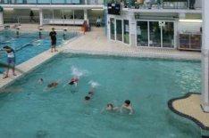 Fronemanstraat 3. Interieur van het Sportfondsenbad Oost met zwemmende kinderen …