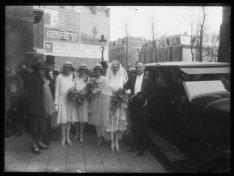 Bruidspaar met entourage op de stoep bij een luxe auto in de Vondelstraat ter ho…