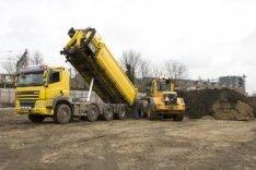 Afgegraven grond op het saneringsterrein Polderweg. Op de achtergrond de Celebes…