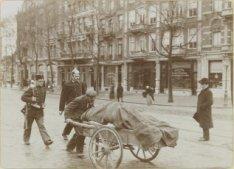 Politeagent en militair begeleiden een man met handkar door de stad. Foto uit al…