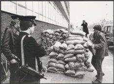 Bewapende politiemannen bewaken het Hoofdbureau van Politie aan de Elandsgracht …