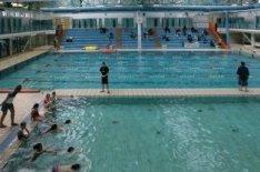 Land van Cocagneplein 44. Interieur van het Sportfondsenbad Oost met zwemmende k…