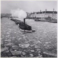 Sleepboot met ijsbreker op de bevroren Amstel